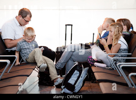 A family in the departure lounge waiting for their flight, Terminal 5, Heathrow airport London UK - Stock Photo