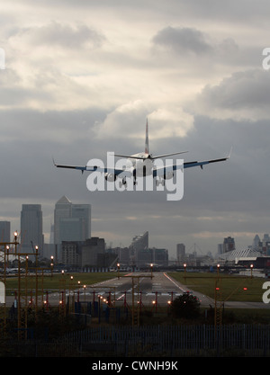 Jet plane landing at London City Airport, with the runway in sight and the financial district visible in the background. - Stock Photo