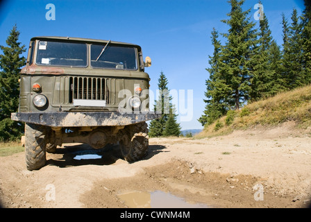truck on a country road with puddles - Stock Photo