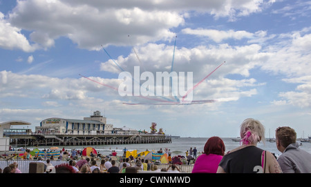 Red Arrows Aerobatic Team flying over Bournemouth Pier with watching crowds on West Beach during the annual Air - Stock Photo