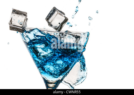 Ice cubes in broken glass with blue martini on white background - Stock Photo