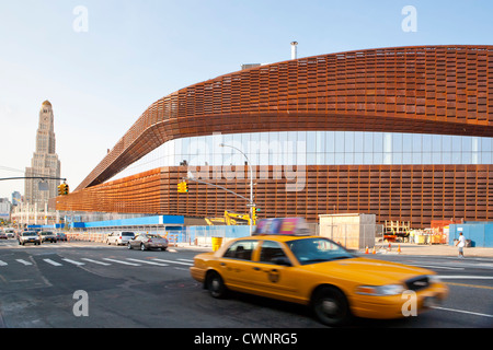 New York City Taxi drives pass the new Barclays Center home of the Brooklyn Nets Sports Arena and Concert Hall. - Stock Photo