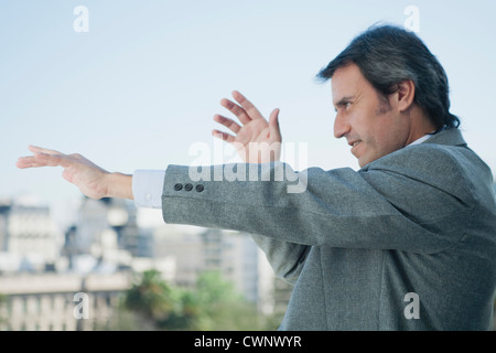 Mature businessman holding arms out in front of him and pointing, looking out of frame - Stock Photo
