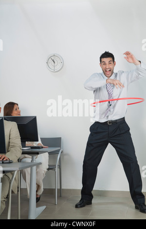 Young businessman playing with hula hoop in office - Stock Photo