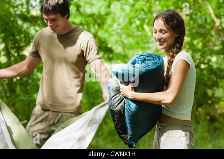 Campers putting away sleeping bag and tent - Stock Photo