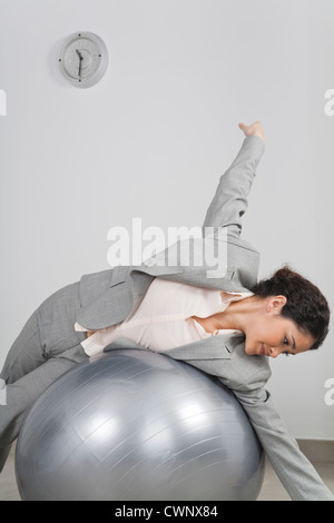 Businesswoman lying on top of fitness ball - Stock Photo