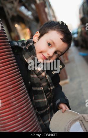 Boy peering around column at camera, portrait - Stock Photo