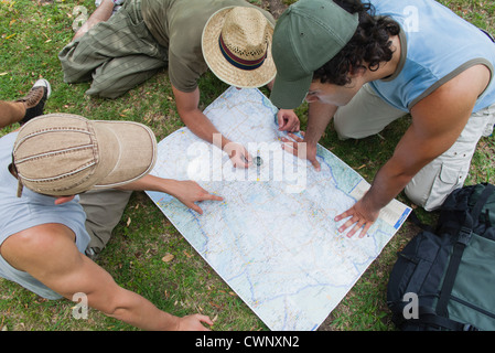 Hikers using compass and looking at map together, high angle view - Stock Photo
