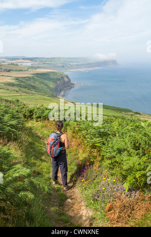 Female hiker on The Cleveland Way national trail coastal footpath near Staithes in North Yorkshire, England, United - Stock Photo