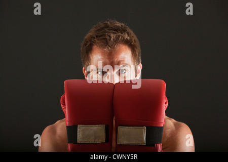 Boxer holding up gloves in front of face in defensive position - Stock Photo