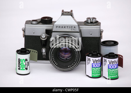 A Praktica 35mm format film camera and various rolls of photographic film. - Stock Photo