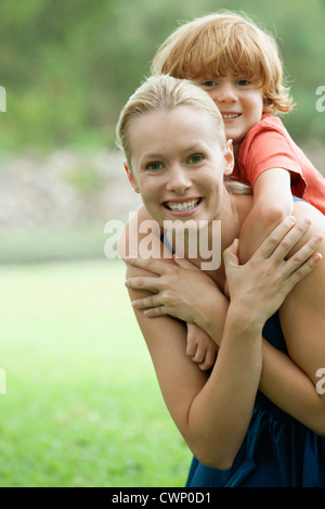 Mother carrying son on back, portrait - Stock Photo