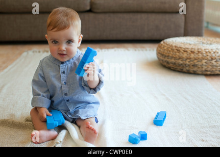 Baby boy playing with building blocks - Stock Photo