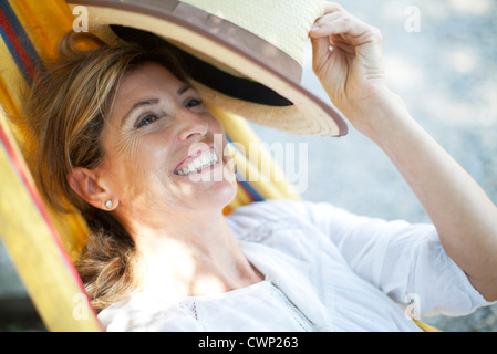 Mature woman relaxing in hammock, portrait - Stock Photo