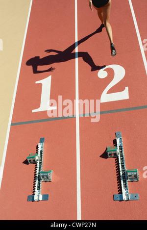 Starting blocks on tracks, athlete leaving starting line - Stock Photo