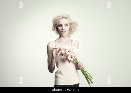 Young woman holding bunch of gerbera daisies - Stock Photo