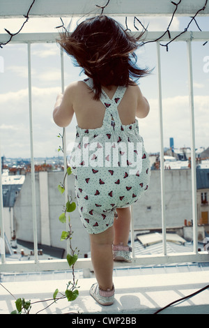 Little girl standing on balcony, looking through railing, rear view - Stock Photo