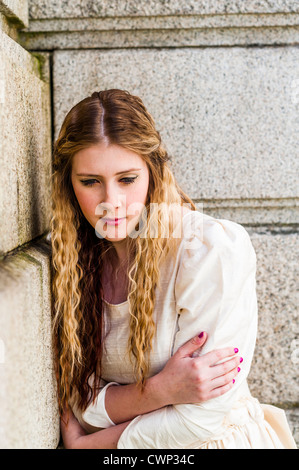 a young sad lonely attractive woman with long blonde hair in an Alt alternative bride fashion shoot, on location UK