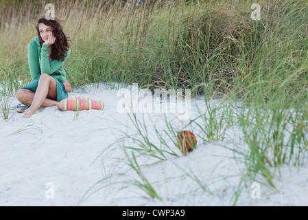 Teenage girl sitting alone on beach, smiling - Stock Photo