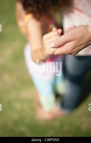 Mother and daughter holding hands, cropped - Stock Photo