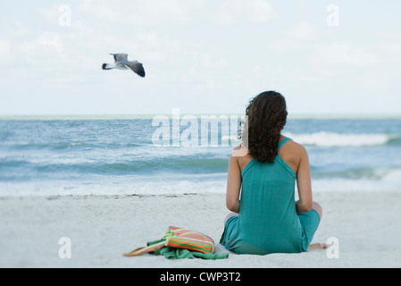 Teenage girl sitting on beach looking at ocean, rear view - Stock Photo