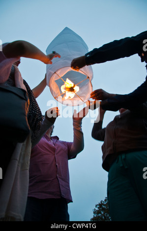 People launching a Chinese paper lantern - Stock Photo