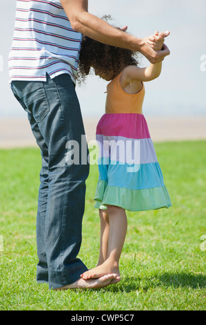 Girl standing on father's feet - Stock Photo