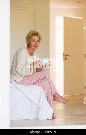 Mature woman sitting on edge of bed with cup of coffee - Stock Photo