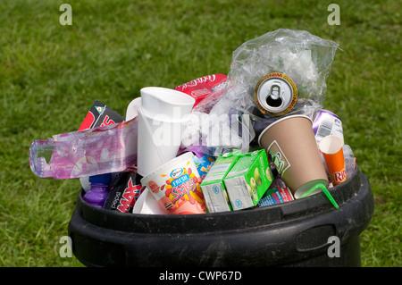Plastic litter bin overflowing with rubbish. - Stock Photo