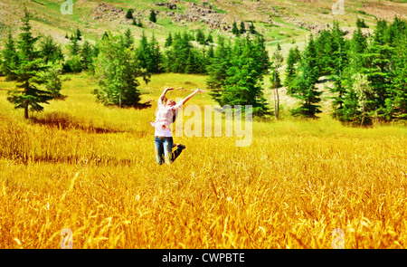 Photo of beautiful girl jumping on golden wheat field in sunny day, picture of active pretty woman playing on rural - Stock Photo