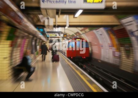 UK. England. London. Tube train arriving at platform of Underground Station. - Stock Photo
