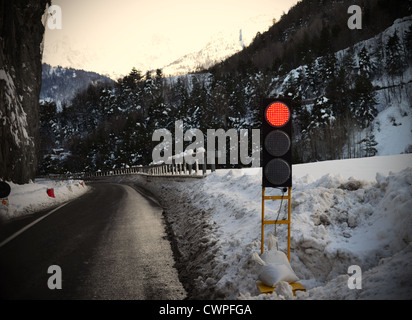 Mountains: red traffic light for avalanche, snowy weather, ice on street - Stock Photo