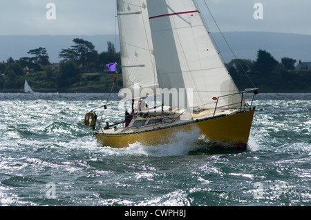 Sailing yachts competing in the JP Morgan Round the Island race in 2012 passed the Needles - Stock Photo
