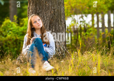 Beautiful teen-girl writing in a notebook while sitting in the park (dreamily looks up) - Stock Photo