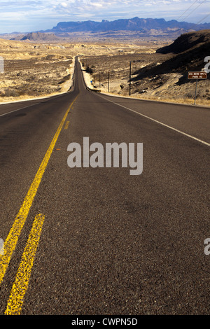 Long straight desert road vanshing into the distance leading to Big Bend National Park, Texas, United States - Stock Photo