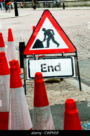 Traffic cones and a sign for road works on a paved street of Cambridge UK - Stock Photo