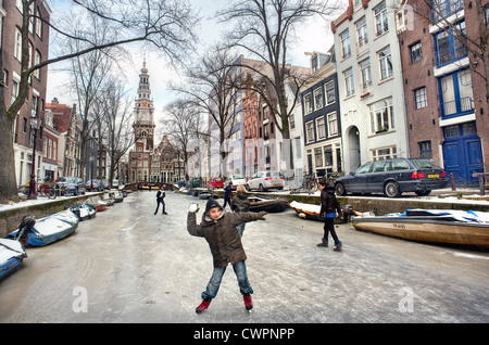 Children throw snowballs while skating on Amsterdam's frozen canals during winter - Stock Photo