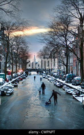 Skaters enjoy the ice on a winter evening on the canals in Amsterdam, the Netherlands. - Stock Photo