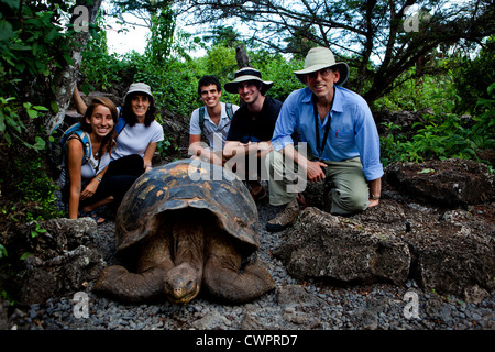 Group posing with Galapagos Giant Tortoise, Galapagos Islands - Stock Photo
