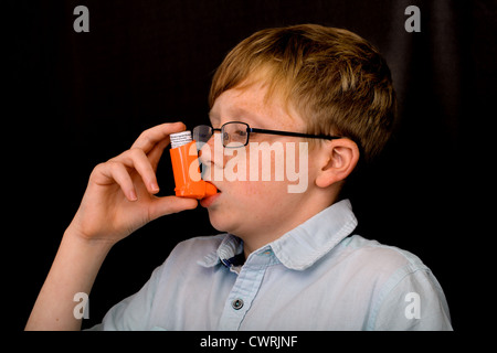 A thirteen year old boy using an asthma pump - Stock Photo