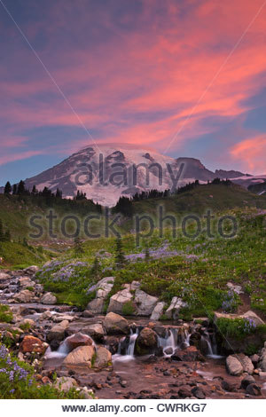 Bright red clouds, illuminated by the sunrise, point to the summit of Mount Rainier in Washington state. - Stock Photo