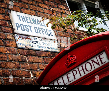 Sign outside the old Thelwall post office with a telephone box nearby - Stock Photo