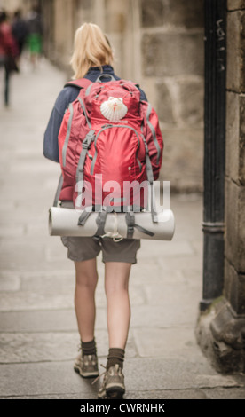 Solo female backpacker walks through the streets of Santigo de Compostela - Stock Photo