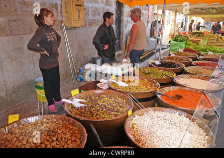 Market traders waiting for customers at stall selling olives mushroms cinnamon and food in Pesenas southern France - Stock Photo