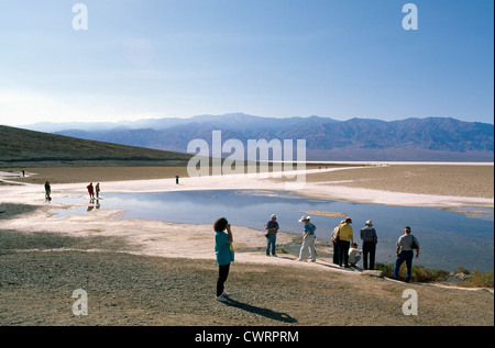 Death Valley National Park, California, USA - Tourists walking on Salt Flats at Badwater Basin, Panamint Mountains - Stock Photo