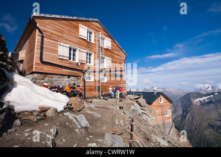 Mountaineers rest up in the warming afternoon sun outside the Mischabel Hut above Saas Fee in the Swiss Alps. - Stock Photo