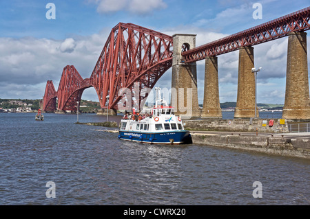The iconic Forth Rail bridge viewed from the South Queensferry promenade with Maid of the Forth with passengers - Stock Photo