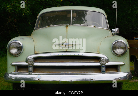 Front view of old green Chevrolet rusting in a field. - Stock Photo