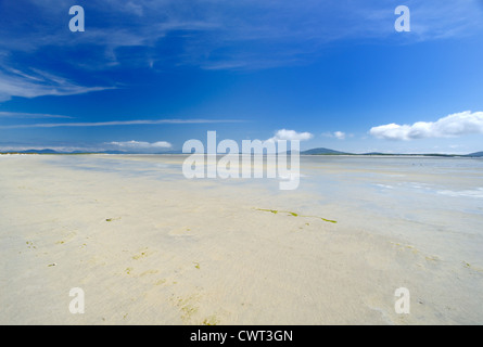 Huge white sandy beach at  low tide with mountains in the distance - Stock Photo