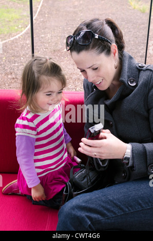 A young mother and her child playing video game in a mobile telephone on a red couch indoors. - Stock Photo